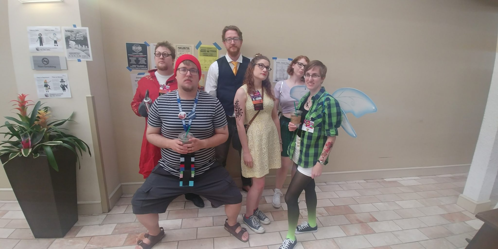 A group of friends dressed as hipster versions of Disney characters stands agains a beige wall, looking unimpressed
