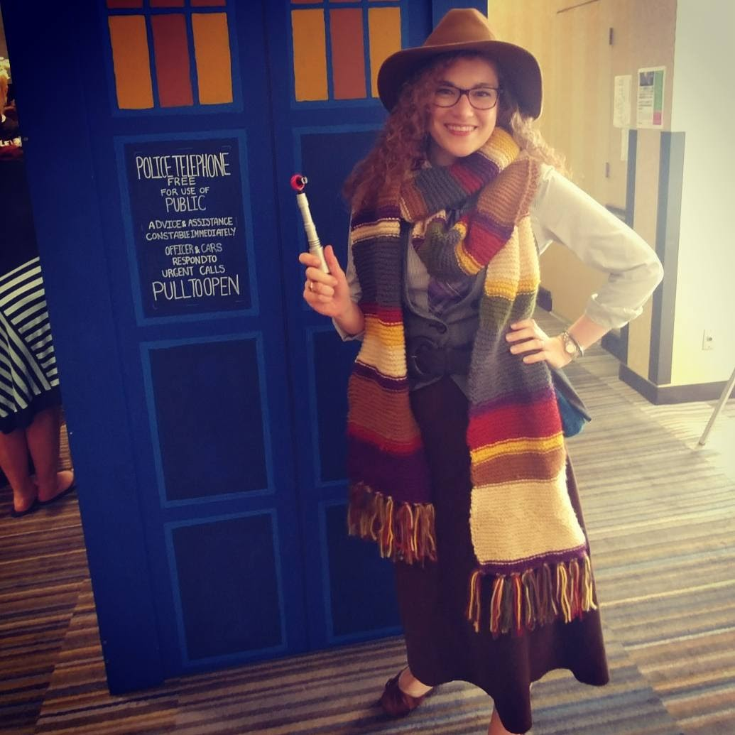 A woman wearing a costume that is a gender-swapped version of the Fourth Doctor from Doctor Who smiles at the camera in front of a cardboard TARDIS, holding up a sonic screwdriver
