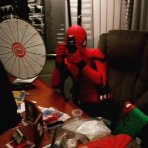 A man dressed as Spider-Man sitting at a cluttered desk and holding a camera up to his eye to take a picture