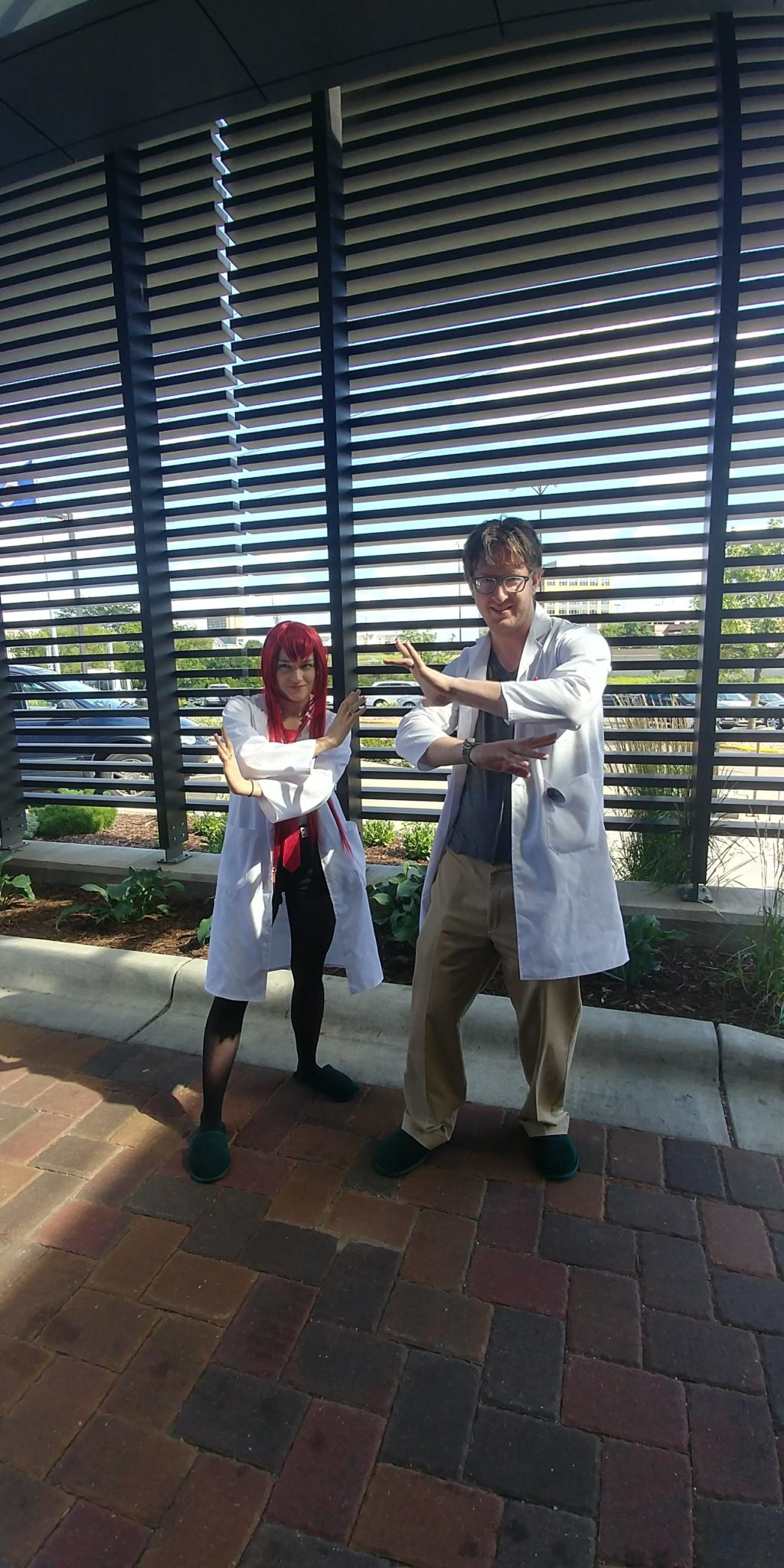 A woman and man dressed as the characters Kurusu and Okabe from Steins;Gate do the classic arms-crossed-in-front-of-chest pose from the show